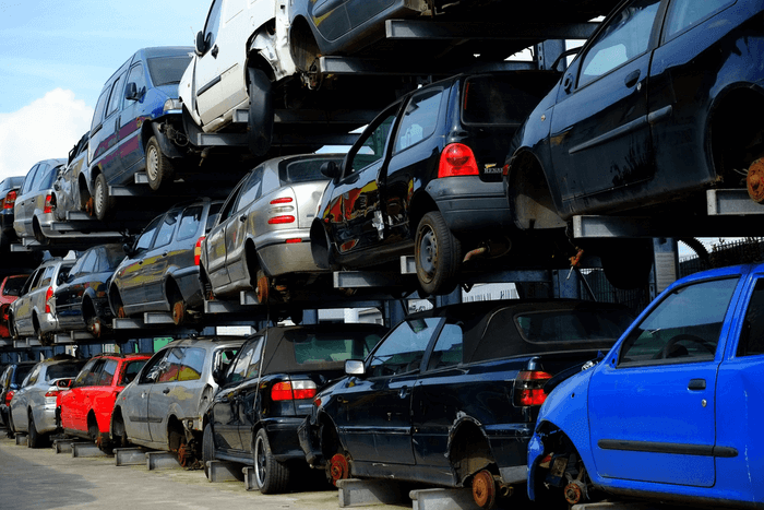 An image of a car scrap yard, with vehicles stacked on top of one another.